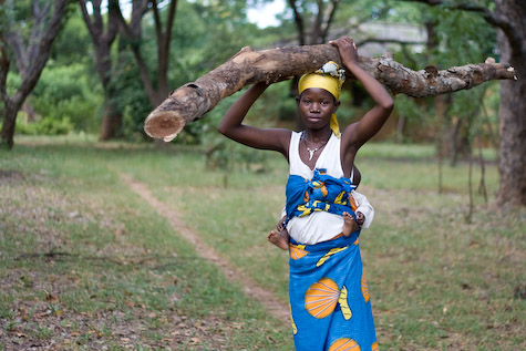 A woman with a baby carries a heavy log AND her baby
